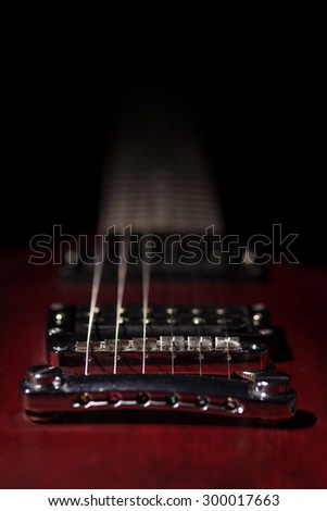 photo guitar, mahogany, electric guitar lying on a black background, poor lighting, musical instrument electronics. - stock photo
