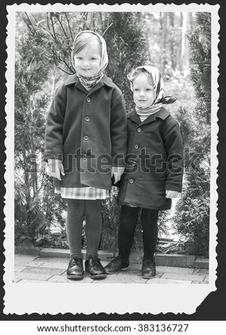 Photo in retro style. Cute little girls (sisters 3 and 4 years) in the tissues. Selective focus. - stock photo