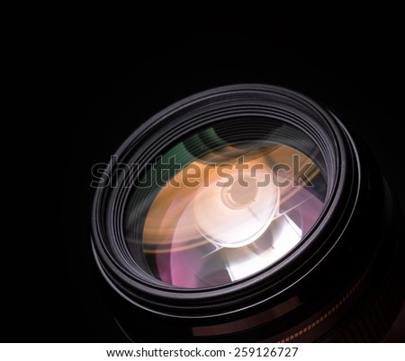 Photo lens closeup with colorful reflections. Black background - stock photo