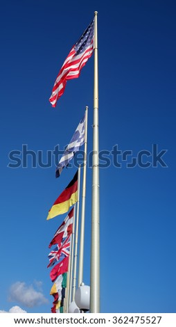 Photo long shot of different national flags flutter in wind on tall flagstaffs in rows against bright blue sky background, vertical picture  - stock photo