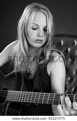 Photo of a beautiful blond female playing an acoustic guitar. - stock photo