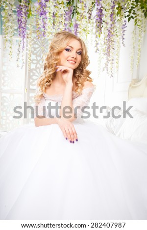 photo of a beautiful brunette bride in a luxurious wedding dress in elegant expensive interior - stock photo
