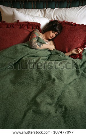 Photo of a beautiful female with tattoos, sleeping alone in a large bed. - stock photo