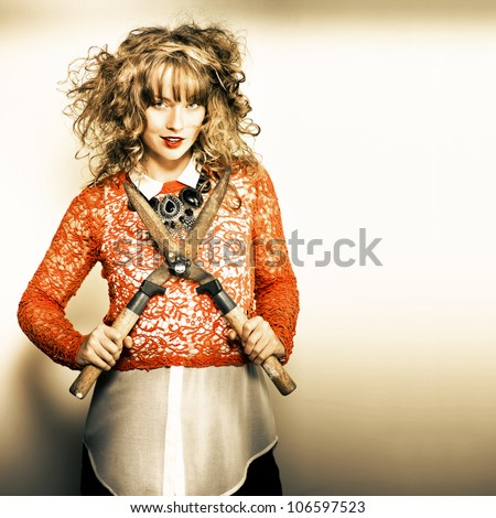 Photo of a beautiful pinup girl in retro style fashion holding a pair of gardening shears in a spring fashion or cut price savings concept - stock photo