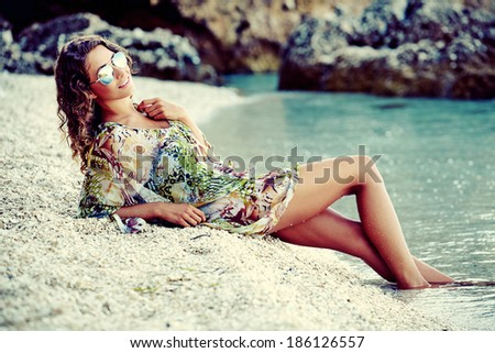 Photo of a beautiful woman in a dress on a adriatic beach - stock photo