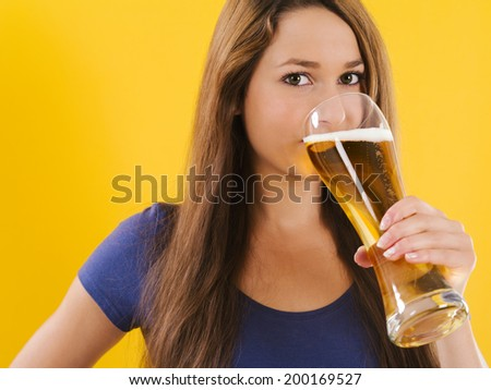 Photo of a beautiful young brunette woman drinking beer from a tall glass. - stock photo