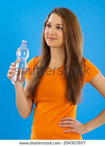 Photo of a beautiful young brunette woman drinking bottled water over blue background. - stock photo