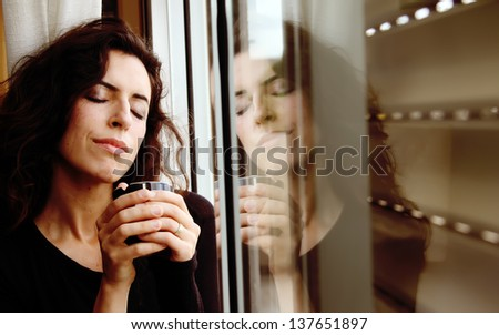 Photo of a beautiful young female drinking coffee and looking out the window - stock photo