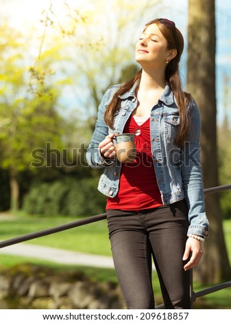 Photo of a beautiful young woman drinking coffee or tea while standing outdoors enjoying the warmth of the sun on her face. - stock photo