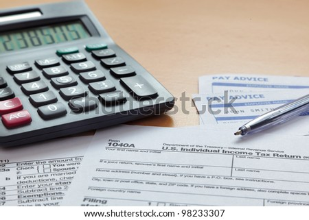 Photo of a blank 1040 tax form with payslips and calculator. The payslip is a mock up the names and all other information on it is fictional. - stock photo
