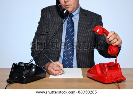 Photo of a businessman sat at a desk with two traditional telephones, one red and one black. He is listening to one call whilst picking up the other phone. - stock photo