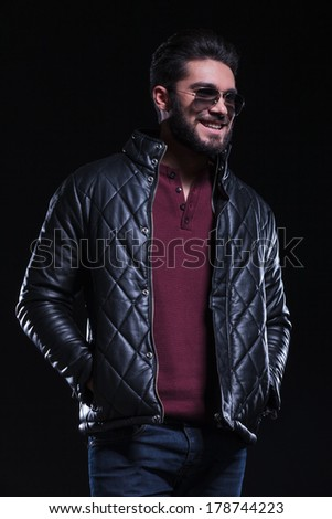 photo of a casual young man smiling away from the camera while holding his hands in his leather jacket pockets. on a black background  - stock photo