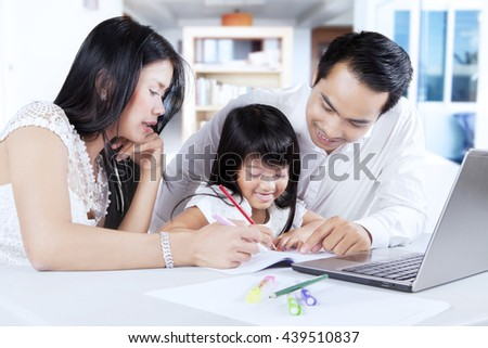 Photo of a cheerful little girl and her parents doing schoolwork while writing on the book and using laptop at home - stock photo