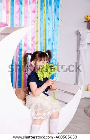 photo of A cheerful little girl with funny tails - stock photo