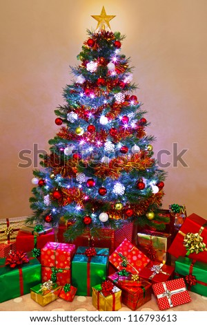 Photo of a decorated Christmas tree lit up with fairy lights and surrounded by gift wrapped presents, Santa has been! - stock photo