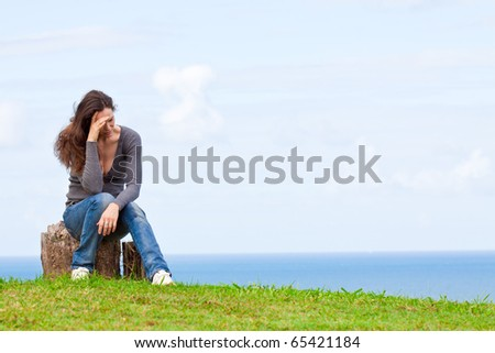 Photo of a depressed and upset young woman sitting outside with her head in her hands - stock photo