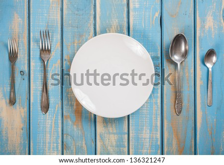 Photo of a dinner set on a blue wooden board - stock photo
