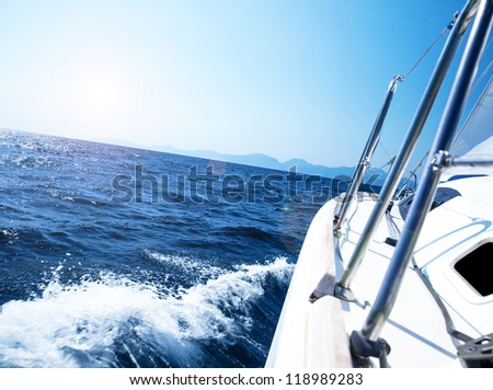 Photo of a 43 foot sailboat in action, speeding at open blue sea, parts of a luxury yacht boat, extreme water sport adventure, freedom and active lifestyle concept - stock photo