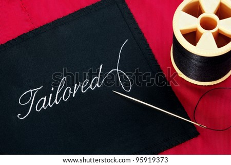 Photo of a garment label with the word Tailored on a red silk lining with a needle and reel of thread. - stock photo
