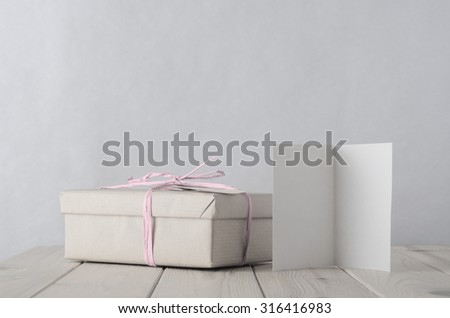Photo of a gift box simply wrapped in brown paper, tied with pale icy pink raffia on an old planked wooden table. A blank open greeting card faces front. Retro style in pale pastel hues. - stock photo