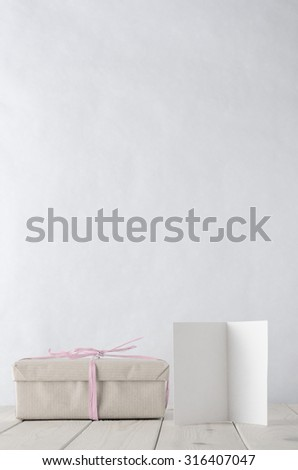 Photo of a gift box wrapped in brown paper, tied with pale icy pink raffia.  A blank open greeting card facing front sits on an old planked wooden table. Processed in retro style with pastel hues. - stock photo