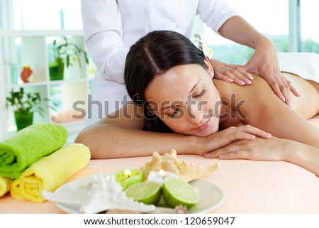 Photo of a girl lying on the massage table, massage therapist doing the procedure - stock photo