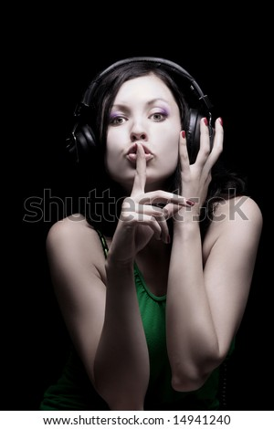 photo of a girl with headphones showing hush - stock photo