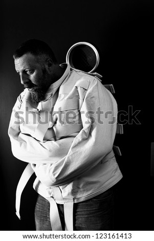 Photo of a insane man in his forties wearing a straitjacket leaning up against an asylum door. - stock photo