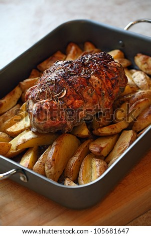 Photo of a lamb roast with potatoes in a roasting pan fresh out of the oven. - stock photo