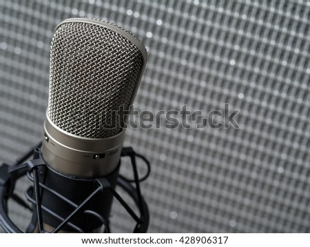 Photo of a large diaphragm studio condenser microphone in a shock mount in front of a guitar speaker cabinet. - stock photo
