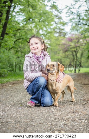 Photo of a little girl with a dog - stock photo