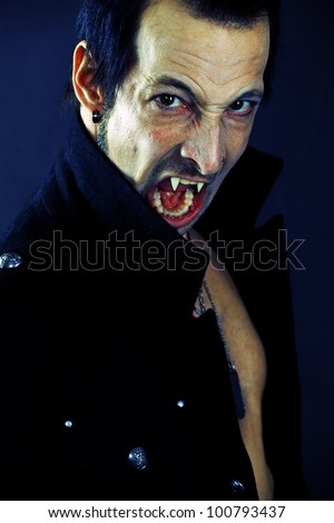 Photo of a male vampire with mouth open and fangs showing.  Harsh lighting and heavily filtered for scarier feel. - stock photo