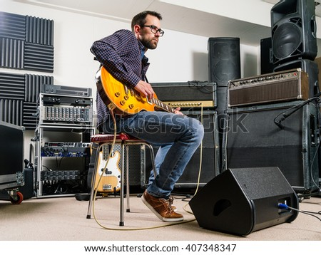 Photo of a man in his late 20's sitting in a recording studio playing his electric guitar. - stock photo