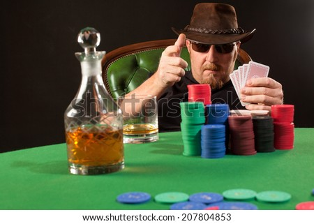 Photo of a man playing poker while wearing sunglasses and a hat.  - stock photo