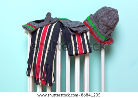 Photo of a mans hat, scarf and gloves drying on an old traditional cast iron radiator, good image for winter related themes. - stock photo
