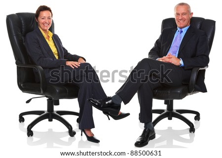 Photo of a mature businessman and businesswoman both sat in a leather executive chairs with their legs crossed and smiling to camera, isolated on a white background with natural chair relection. - stock photo
