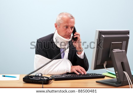 Photo of a mature businessman with injuries talking on the phone whilst trying to work on his computer. Good image for health and safety or accident at work related themes. - stock photo