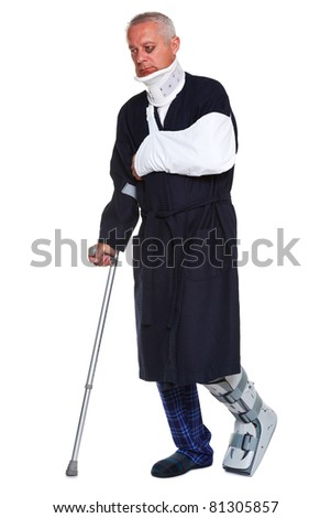Photo of a mature male with various injuries using a crutch, he's wearing a neck brace, arm sling and leg cast and has a black eye, isolated on a white background. - stock photo