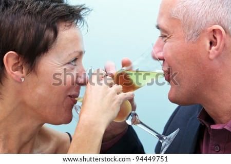Photo of a mature married couple drinking glasses of champagne and looking into each others eyes. - stock photo