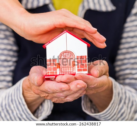 Photo of a miniature house holding in hands - stock photo