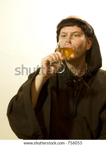 Photo of a monk looking enjoying a good glass of wine. - stock photo