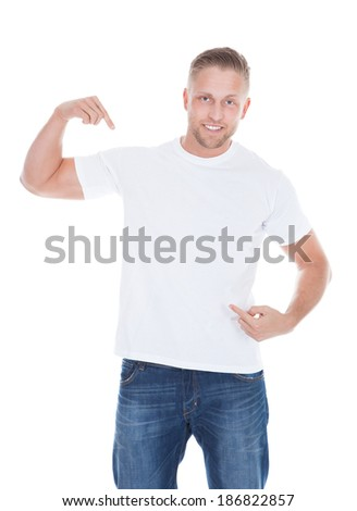Photo of a muscular man pointing his fingers at the front of at his blank white t-shirt with copyspace for your text or logo - stock photo