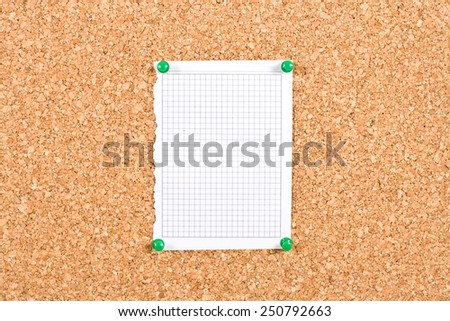 Photo of a piece of squared paper taken out of a notebook, the paper is pinned to a cork board, the photo is ideal as background for informations. - stock photo