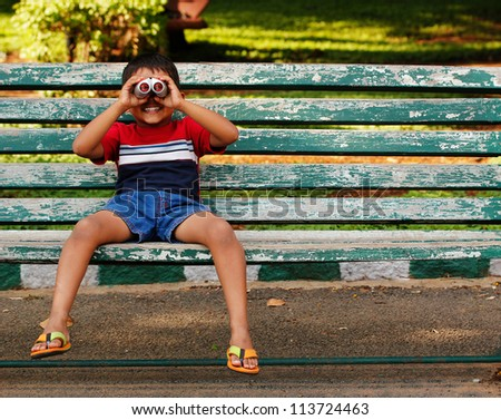 Photo of a playful and cute young asian/indian boy looking into binoculars and having fun at a park. The child is sitting on a old wooden chair in a garden on a sunny afternoon and having good time. - stock photo