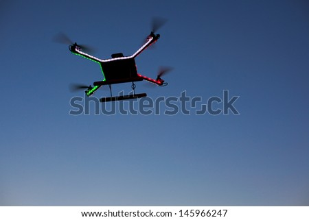 Photo of a quadrocopter on blue sky - stock photo