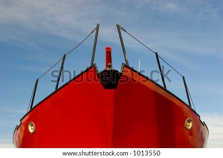 Photo of a red fishing boat in dry dock against blue sky - stock photo