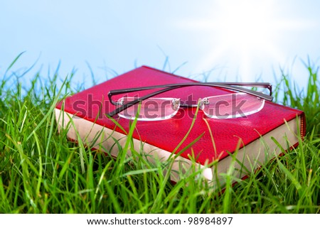 Photo of a red hardback book in grass on a sunny day with spectacles on top. - stock photo