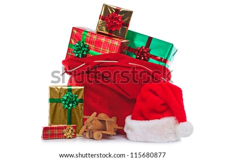 Photo of a red Santa Claus hat and sack full of gift wrapped presents and toys, isolated on a white background. - stock photo