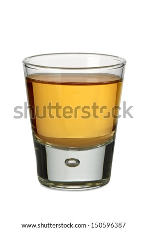 Photo of a shot glass filled with whiskey or bourbon. - stock photo