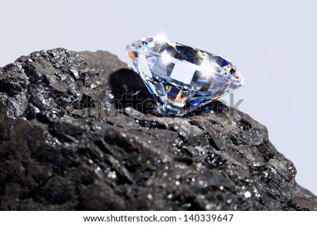 Photo of a single cut diamond on a piece of coal against a plain background. - stock photo
